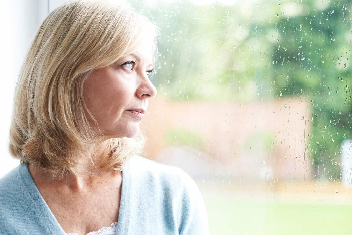 donna triste davanti alla finestra