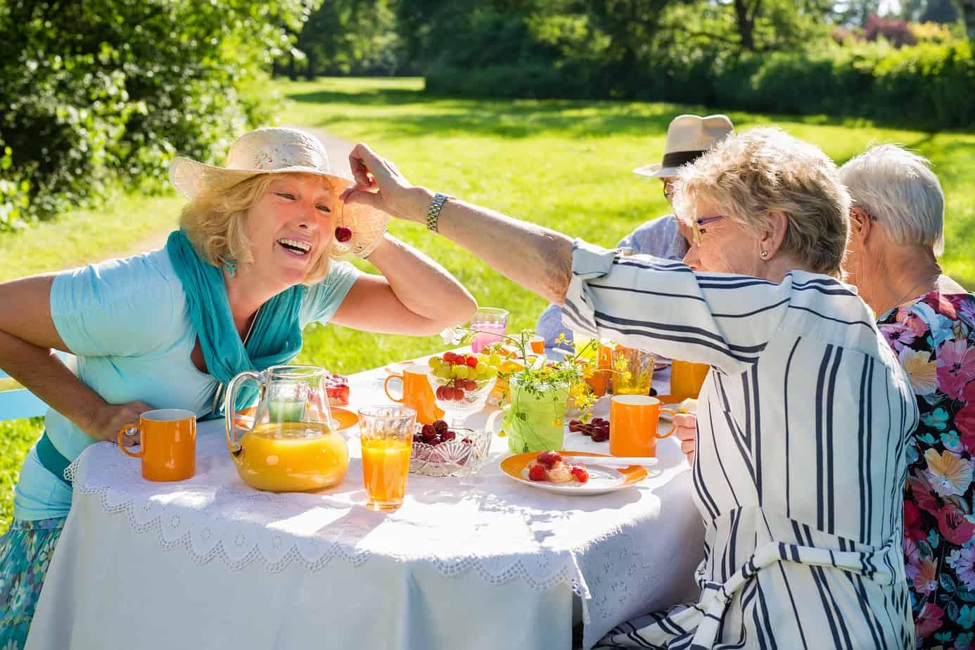 gruppo di anziani felici fanno picnic in giardino