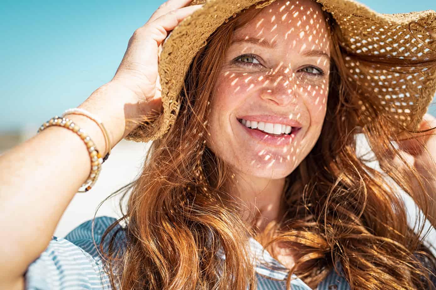 donna sorridente con cappello in spiaggia