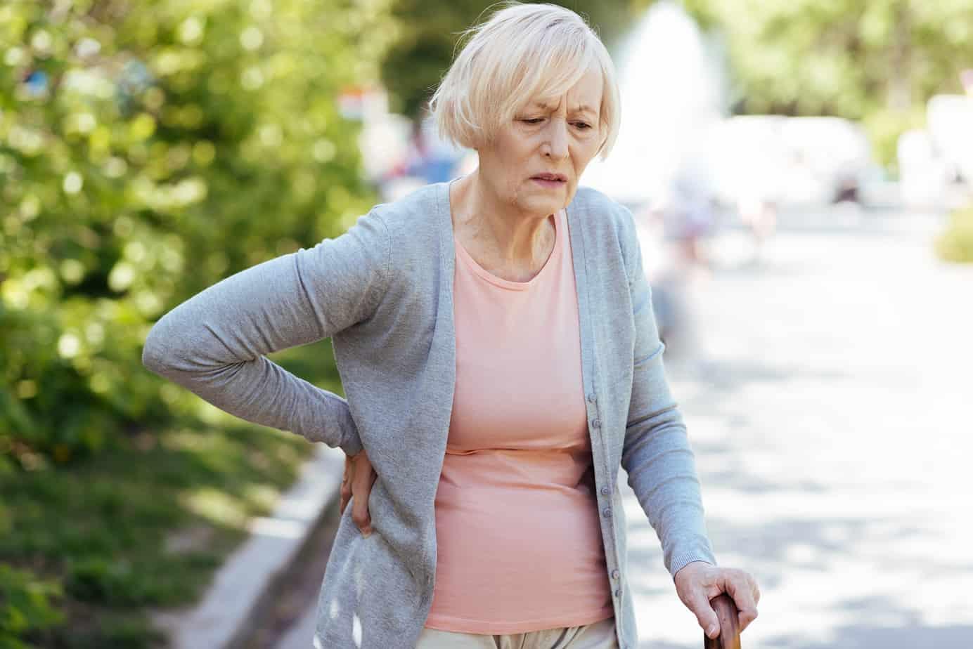 donna cammina con mal di schiena