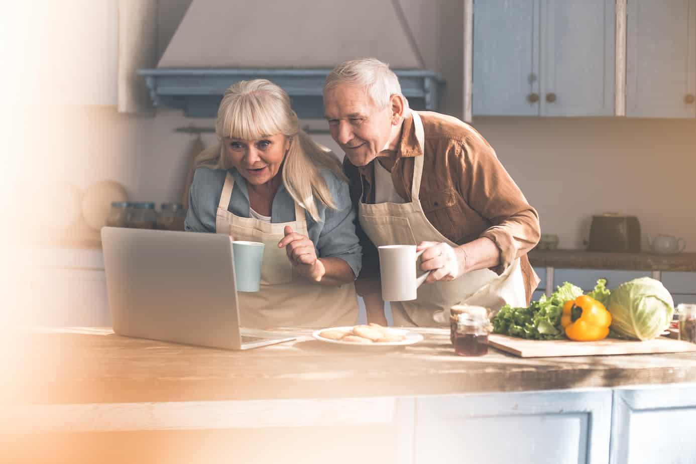 coppia anziana sta guardando ricette online in cucina