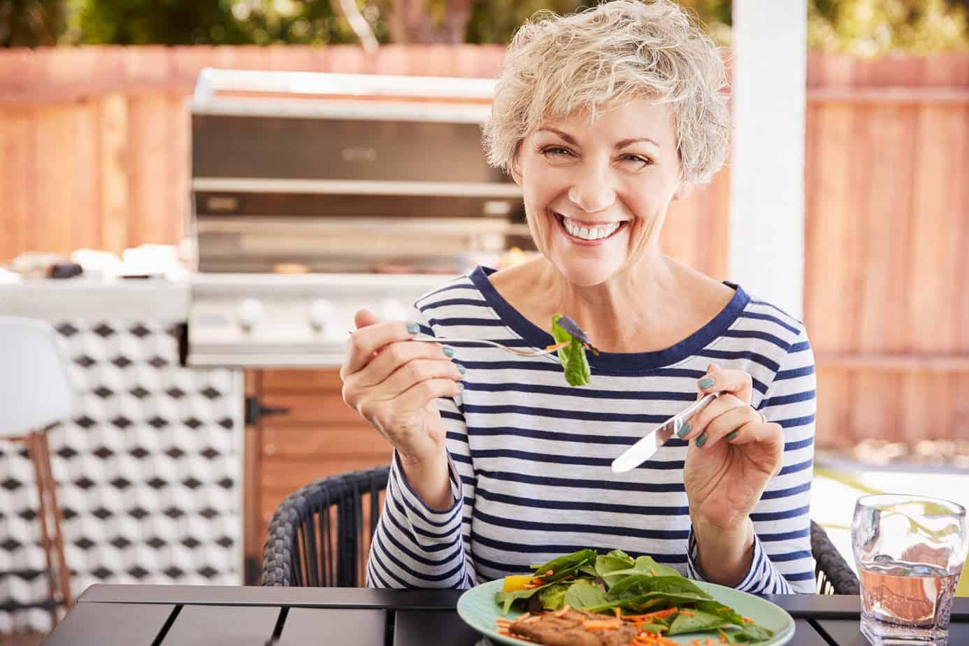 signora allegra sorride mentre mangia insalata