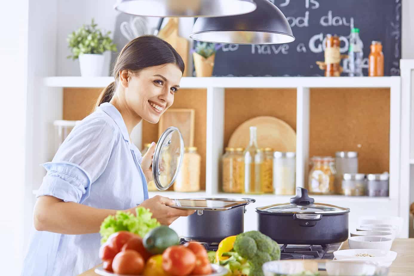 signora felice prepara da mangiare in cucina